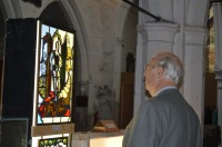 Fig. 1. Artist Sep Waugh looks at panels by Harry Harvey. Photo by Megan Stacey.
