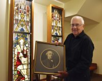 Fig. 2. Dick Clayton holds a photo of his great-grandfather, John Richard Clayton, co-founder of Clayton and Bell, in front of stained glass by the company, recently pur-chased by Clayton.